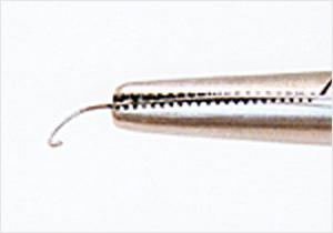 フックを下に向け、持針器の先端でプレート部を挟む